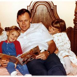 Author Gerald Lund reads a book to his young children. His daughter Rebecca, right, grew up to share his love of writing and has now published three books of her own.
