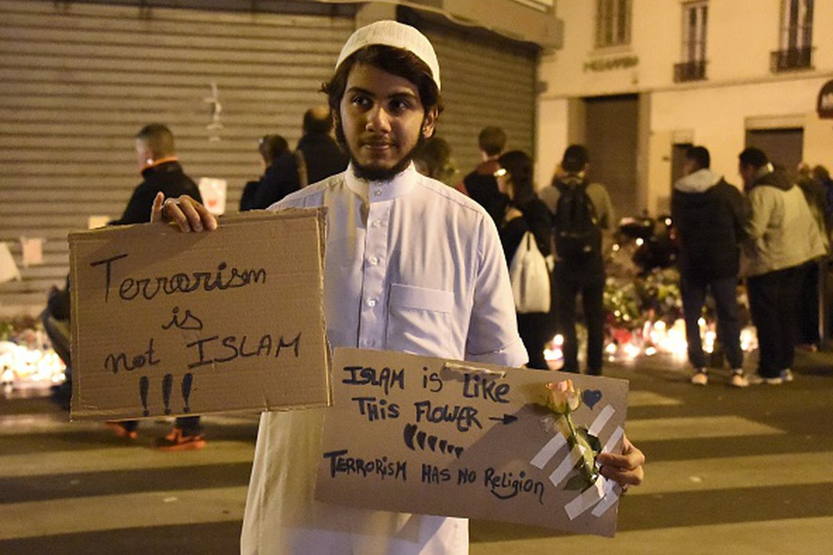"""A Muslim holds placard reading """"Terrorism is not Islam. Islam is like this flower. Terrorism has no religion,"""" during a gathering at Le Carillon restaurant one of the site of the attacks in Paris, on November 15, 2015, in the 10th district of Paris."""