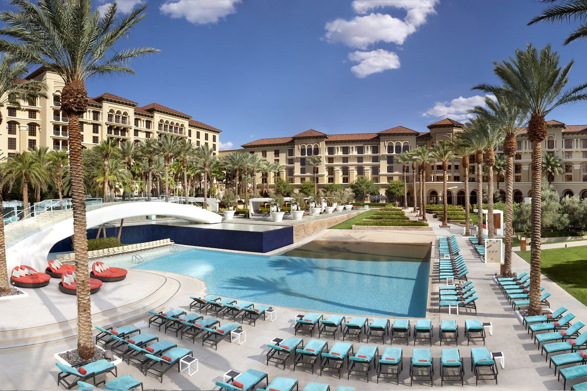 A pool with lounge chairs, palm trees, and a hotel in the background