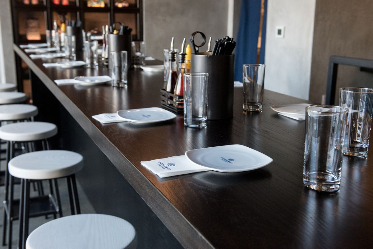 A view of a communal table at Momosan, with empty glasses, white plates, condiments, and chopsticks on display.