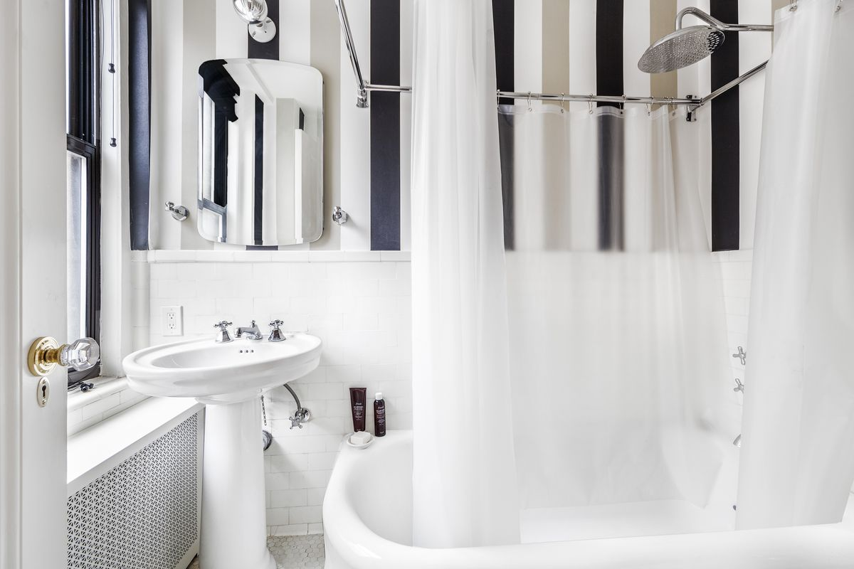 A bathroom with white tiles and painted stripes on its walls.