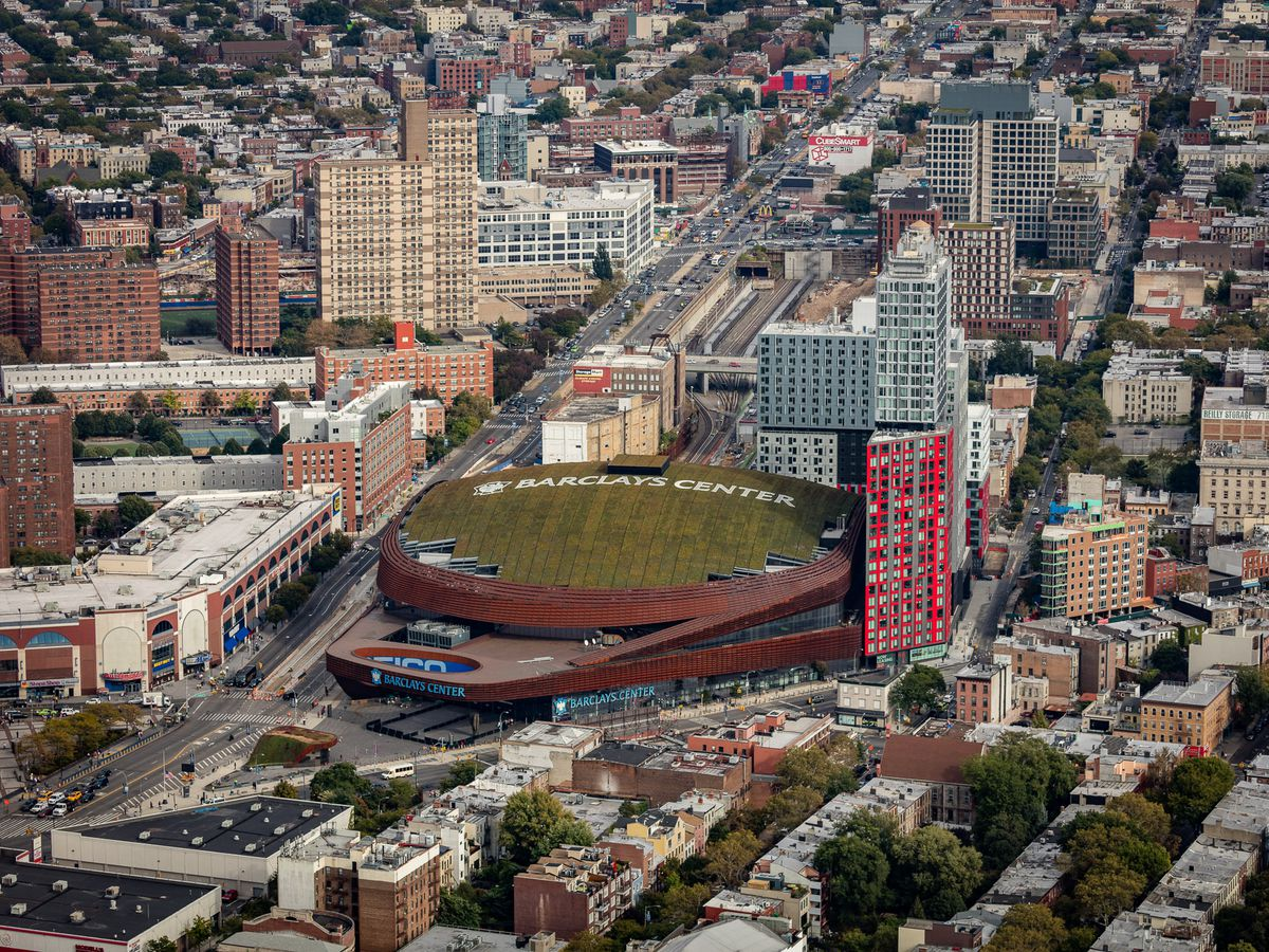 An aerial view of city buildings and a sports stadium.
