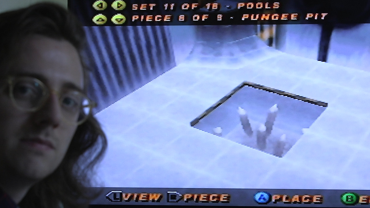 """The """"pungee pit"""" asset from Tony Hawk's Pro Skater 2 is displayed on a TV behind Brian David Gilbert, who is looking judgmentally into the camera."""