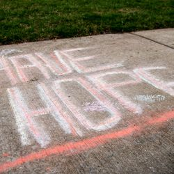 """""""Have Hope"""" is written in rain-faded chalk on the sidewalk outside a home in the 10000 block of Drury Lane in Westchester, Monday, April 6, 2020."""
