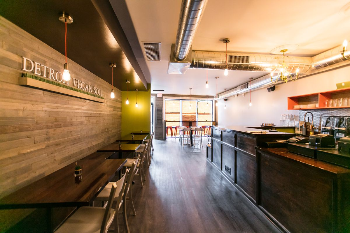 The vacant interior of Detroit Vegan Soul features lots of natural wood tones, green walls, and a long counter.