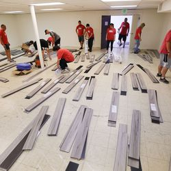 """Ken Garff volunteers install flooring as part of a 3-day makeover project at Lehi American Legion Post No. 19 in Lehi on Tuesday, June 22, 2021. The project is part of Ken Garff's """"We're 'Hear' for You"""" initiative that is committed to reaching out to community groups and organizations and help them recover from the effects of the pandemic."""