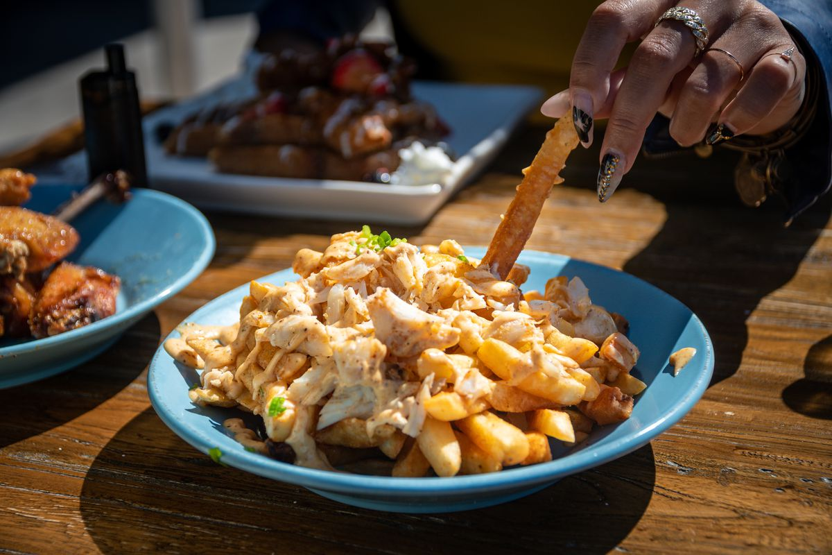 A blue plate of fries covered in lump crab meat.