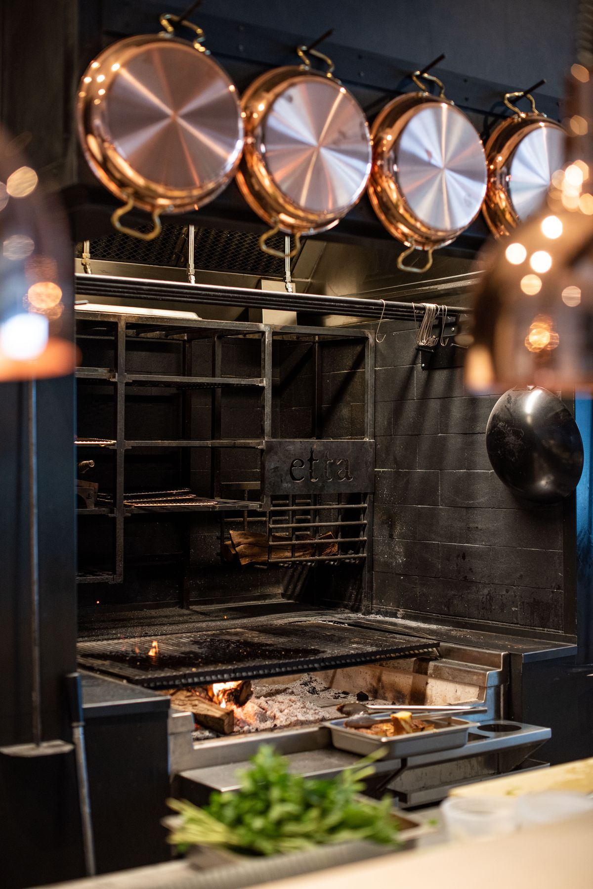 A vertical photo of a deep black metal hearth with wood as fuel to cook meats.