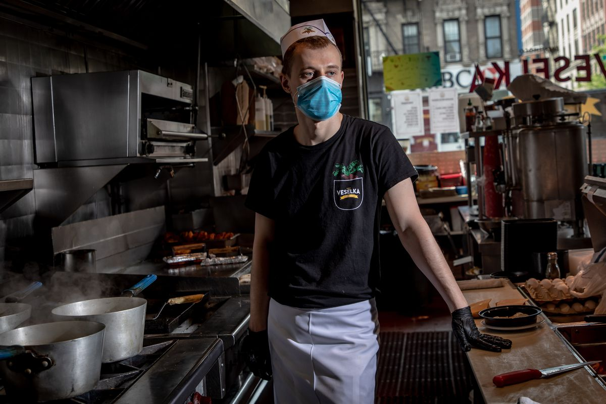 Vitalli, clad in a black t-shirt and a blue face mask, poses for a photo while working the grill