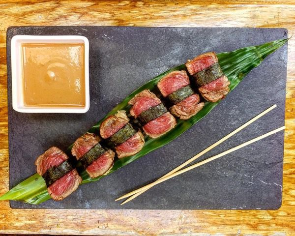 From above, a row of beef cuts bound with nori (presumably to rice below) laying on a tropical leaf on a slate charcuterie board with a bowl of dipping sauce and chopsticks
