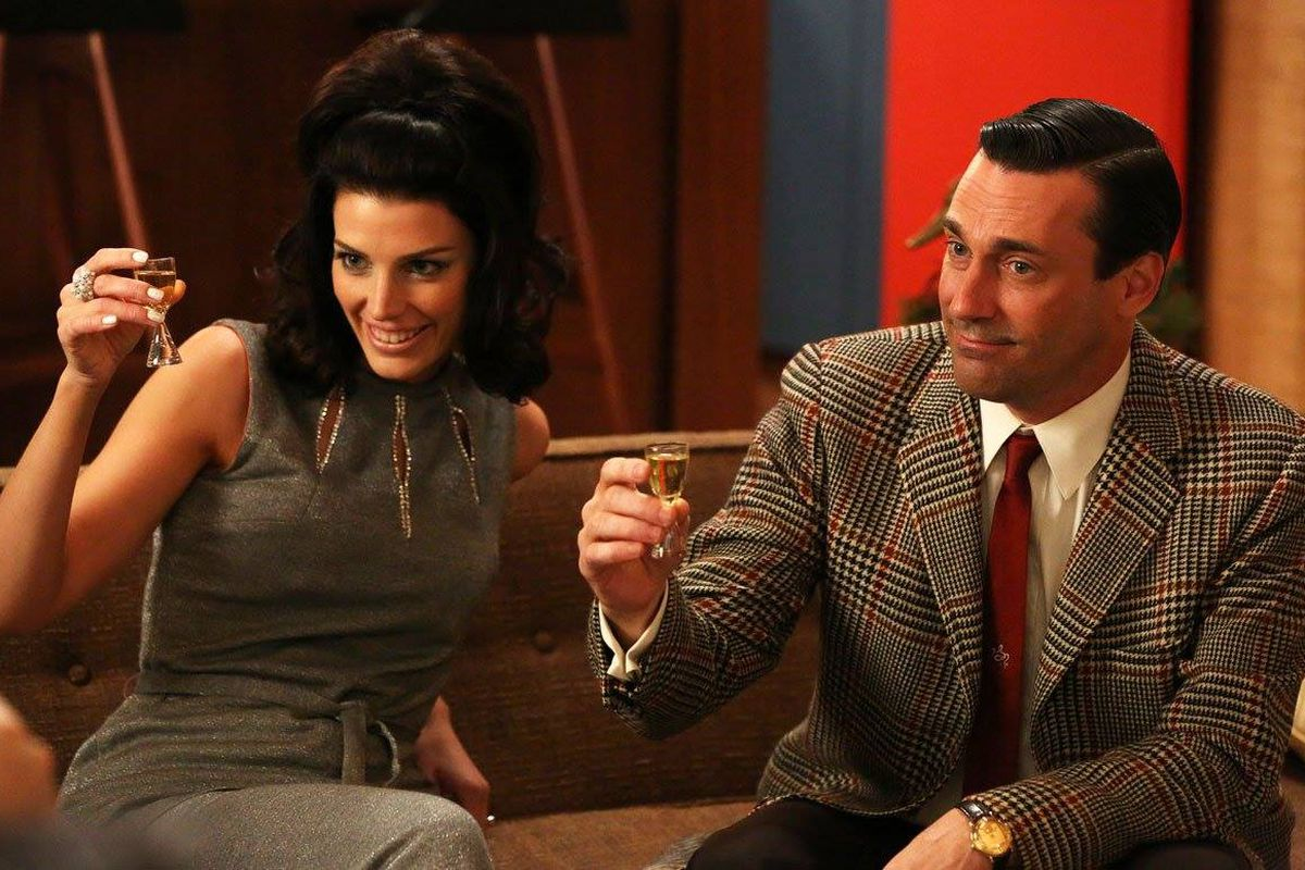 Characters Megan and Don Draper from TV show Mad Men raising a toast. She has on a sleeveless jumpsuit and he has on a plaid sports coat and tie. They are seated. Her hair is in a semi-bouffant and his is slicked back.