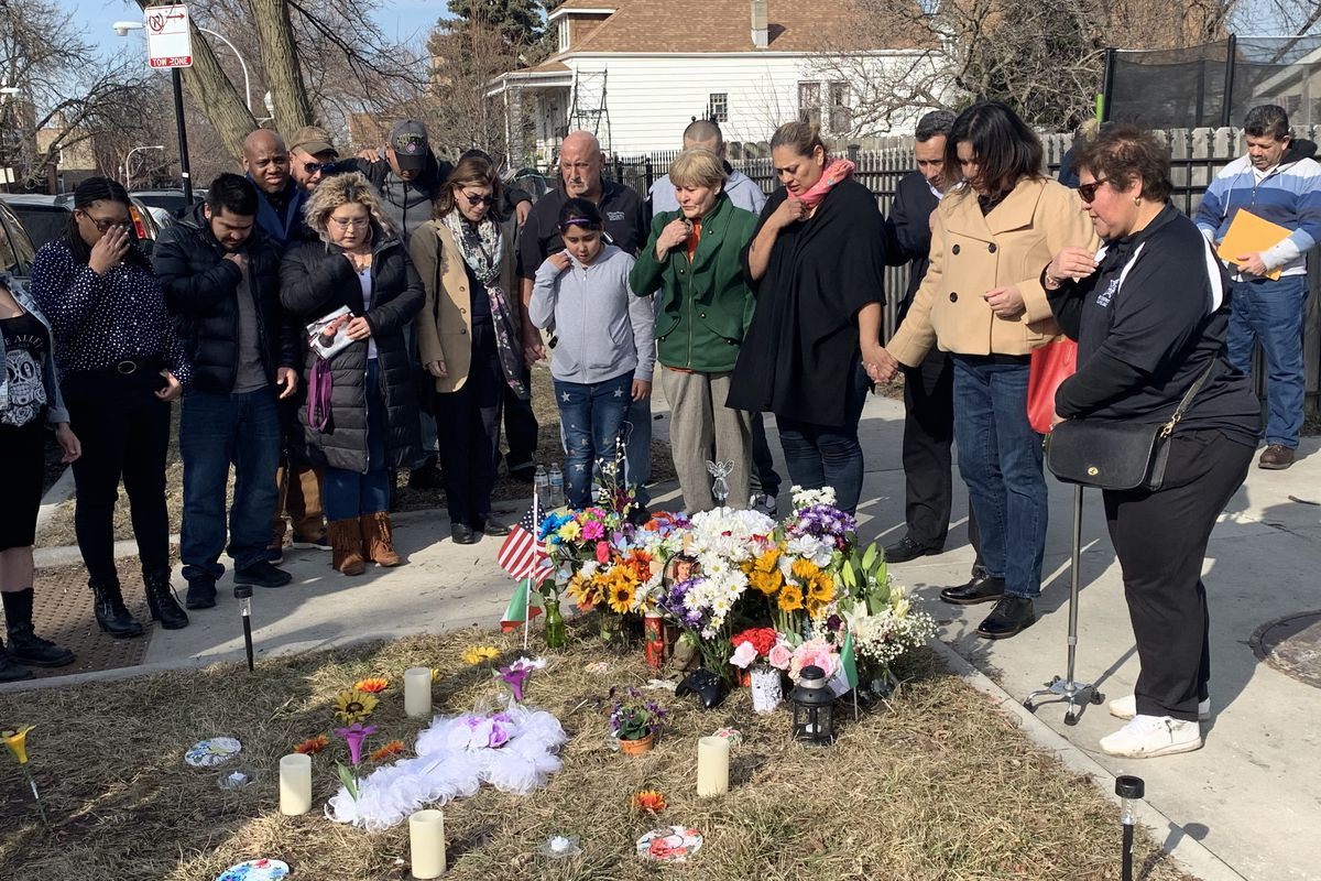 Friends and family of Frank Aguilar, a nurse who was fatally shot in Little Village last year, gather in prayer at his memorial site Sunday.