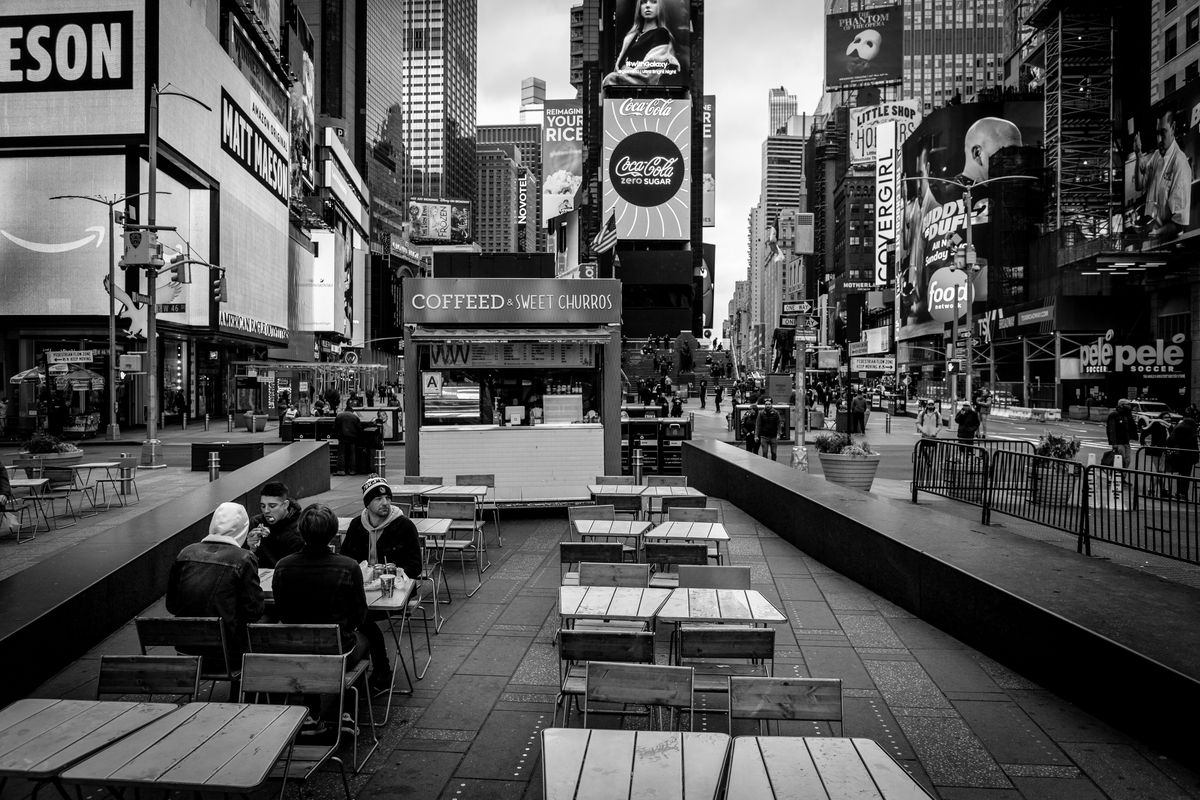A black and white photo of Times Square showing people sitting at tables and billboards in the back