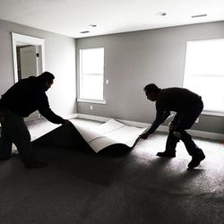 Jesus Lopez, left, and Louis Gomez install carpet at a new home in Farmington on Thursday, Feb. 4, 2016.
