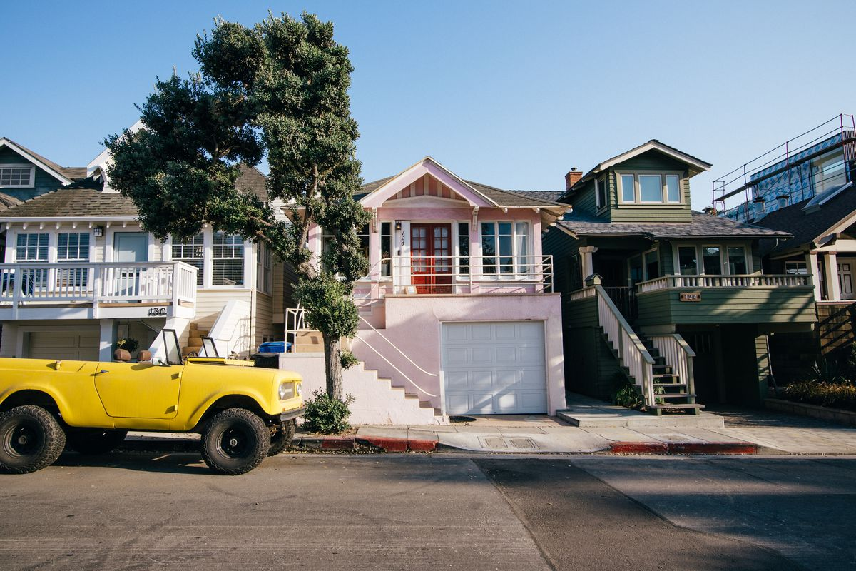 A residential street with homes—in shades of pink, cream, and green, packed tightly together. A yellow jeep is parked out front.