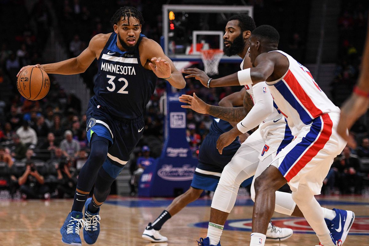 Minnesota Timberwolves center Karl-Anthony Towns drives to the basket as Detroit Pistons forward Tony Snell and center Andre Drummond defend during the first quarter at Little Caesars Arena.