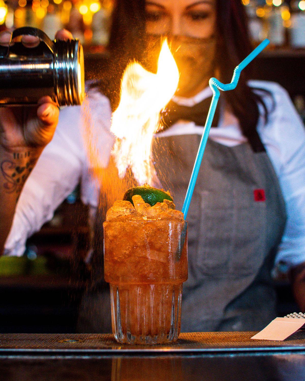 A Nickel City bartender making a Flaming Moe