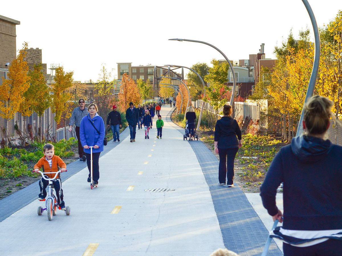 A path with people walking, running, and riding bicycles. There are trees and grass on both sides of the path.