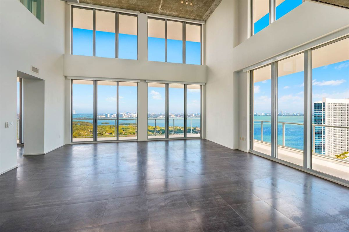 double-height ceilings in a midtown miami penthouse with bay views and floor-to-ceiling windows