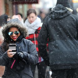 Karla Lemus smiles as she looks at a selfie she just took of herself as she and others walk the sidewalks on Main Street in Park City as they attend Sundance on Sunday, Jan., 22, 2017.