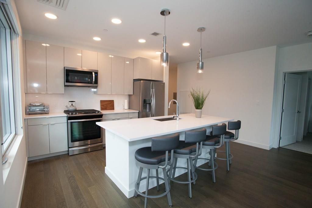 An open kitchen-living room area facing the kitchen over its island.