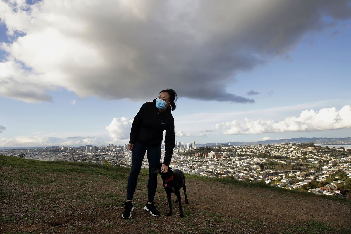 A woman in a breathing mask and a dog seen atop Bernal Heights with the city of San Francisco in the background.