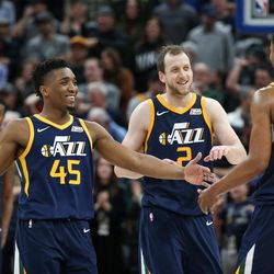 Utah Jazz guard Donovan Mitchell (45), forward Joe Ingles (2) and guard Rodney Hood (5) celebrate in the final moments of their 104-101 win over the Cleveland Cavaliers at Vivint Arena in Salt Lake City on Saturday, Dec. 30, 2017.