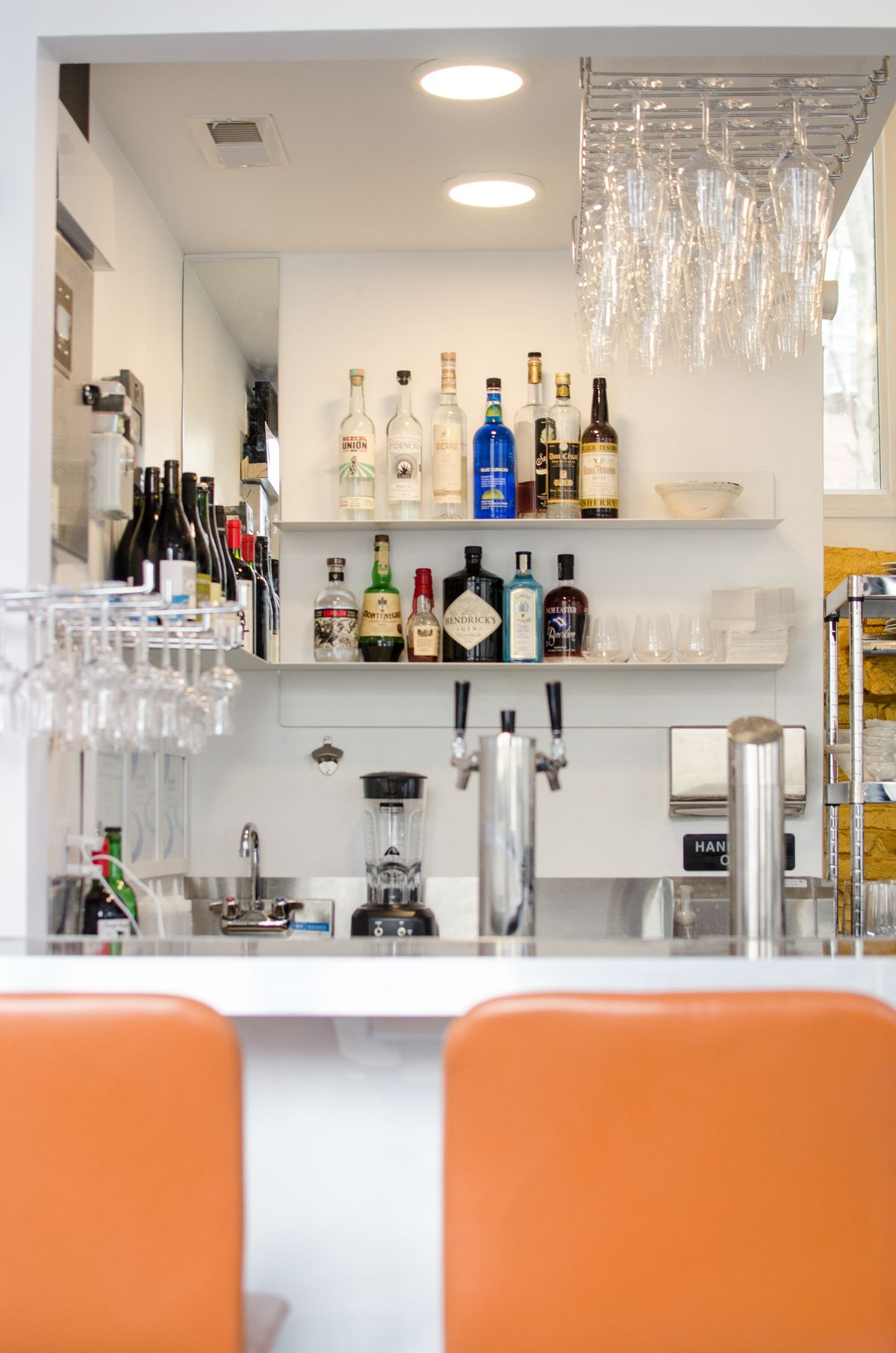 A vertical image shows a slice of a small restaurant's interior, with orange stools at a white bar and two small shelves of liquor