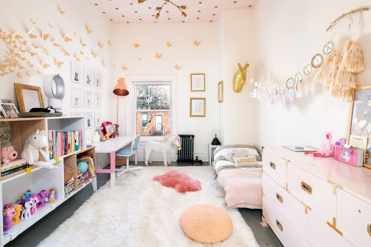 A top-floor kids room features high ceilings, a plush white area rug, and pink accents.