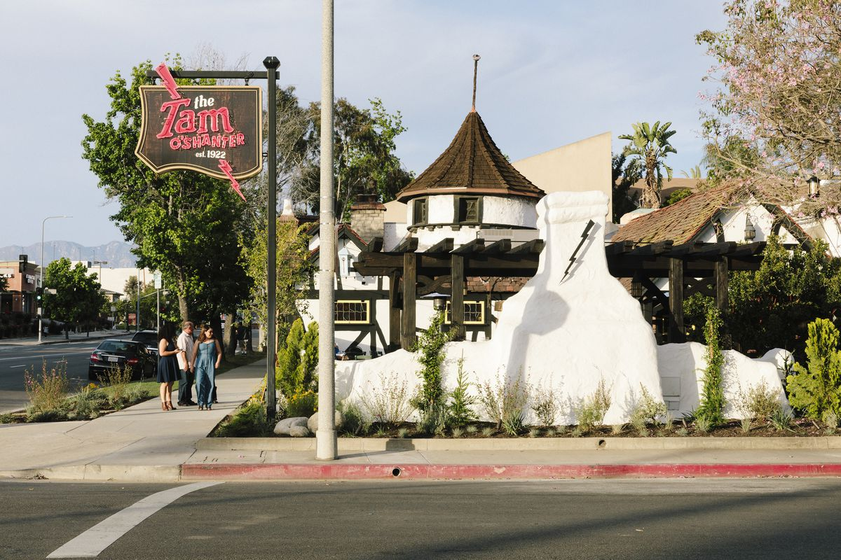 """The Tam O'Shanter restaurant at present day. It has a turret with a timber roof and a wood and neon sign that reads """"The Tam O'Shanter established 1922."""""""