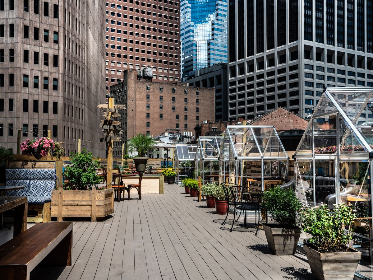 A rooftop deck lined with several greenhouses, which each contain a set of tables and chairs