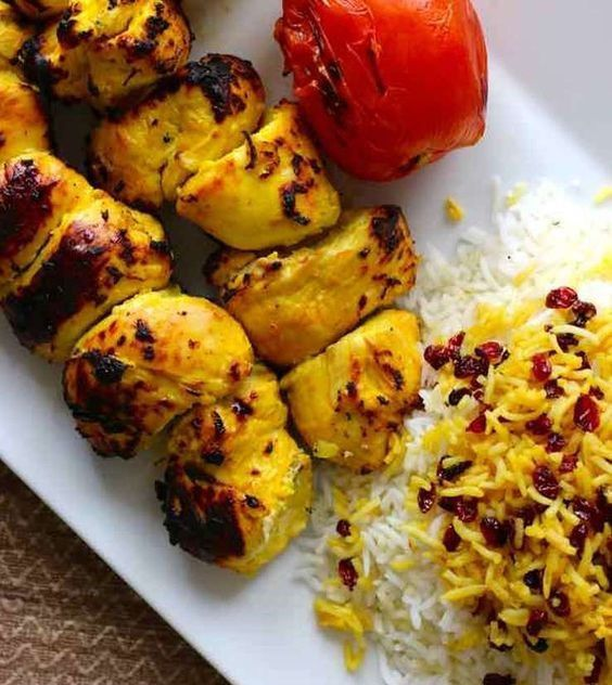 Two chicken kebabs next to a mound of seasoned Iranian rice.