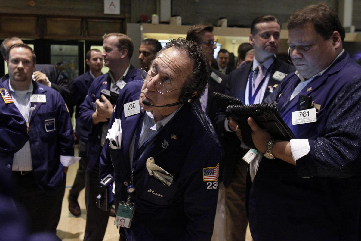 In this Friday, Aug. 3, 2012 file photo, trader Steven Kaplan, center, checks prices as he waits for shares of AIG to resume trading on the floor of the New York Stock Exchange.