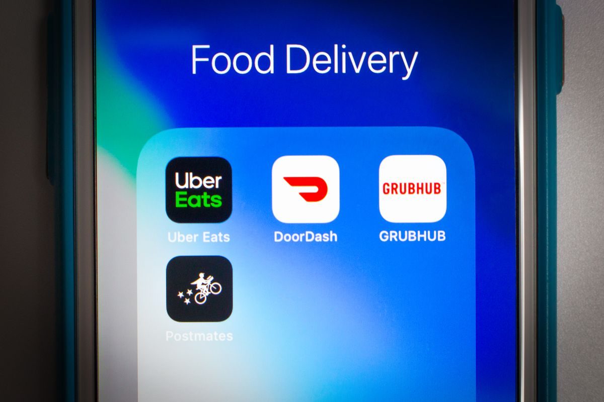 An iPhone shows app icons for Uber Eats, DoorDash, GrubHub, and Postmates.