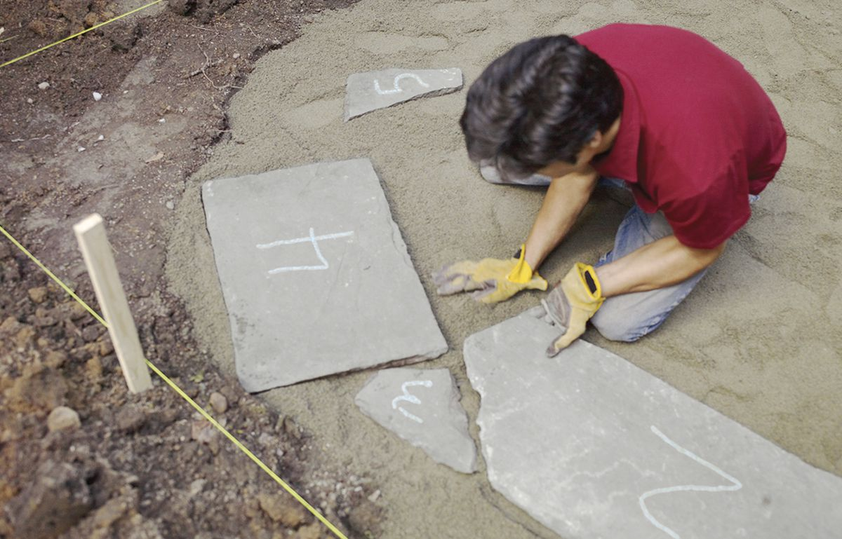 Man Lays Out Numbered Stones For Bluestone Patio