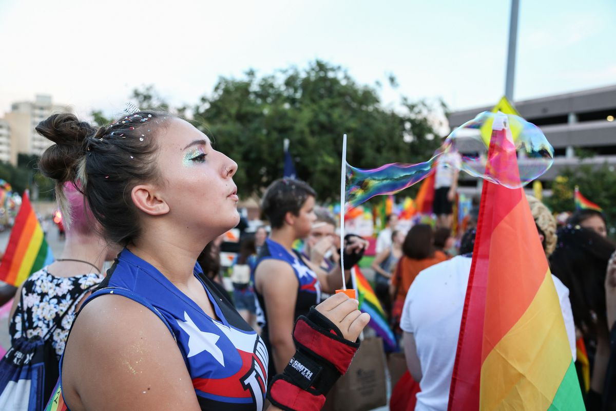Photo of a woman blowing a soap bubble with Pride flag