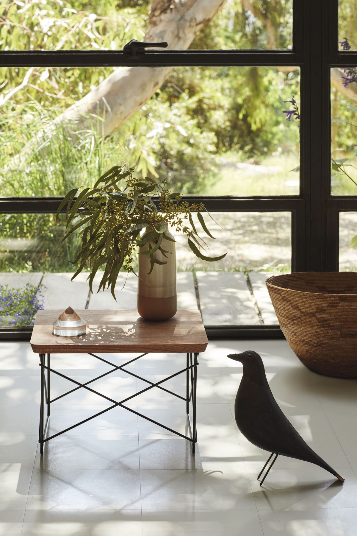 A small table with wire frame base and wooden top holds a plant on top.