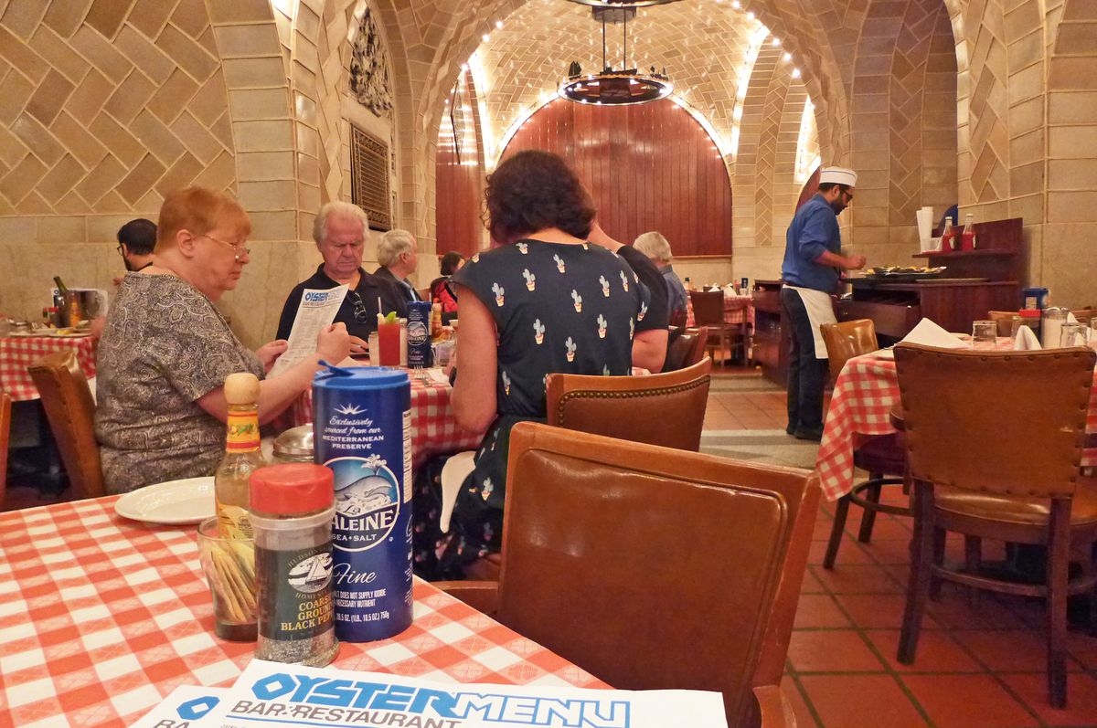 In the foreground, an empty table with a red checked tablecloth, in the background a table of four diners...