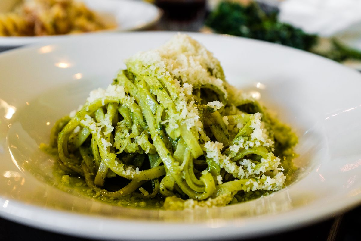 A green-tinged pasta dished covered in parmesan cheese.