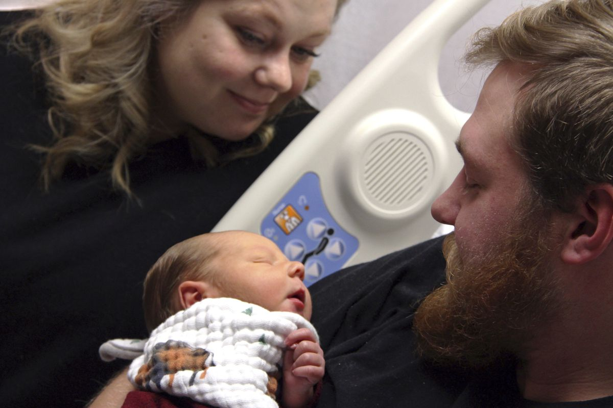 In this Tuesday, Oct. 23, 2018, photo Andrew Goette and his wife, Ashley, look at their baby, Lennon, at United Hospital in Saint Paul, Minnesota. Andrew awoke from a medically-induced coma just in time for the birth of Lennon after his wife, 39 weeks pre