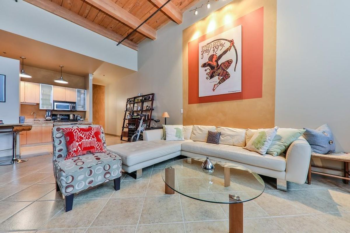 A living room with a sectional couch, a large print of someone shooting a bow on the wall, and very high ceilings.
