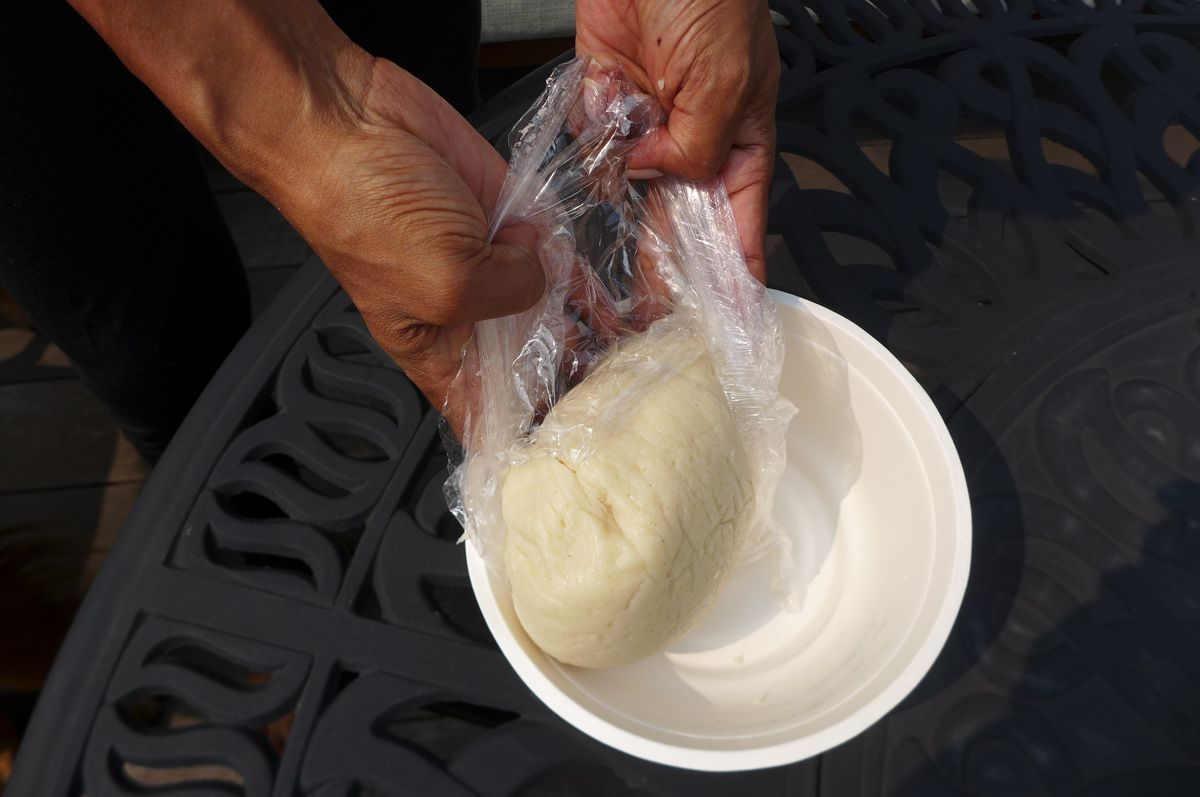 Two hand remove plastic wrap from a ball of fufu and let it tumble into a plastic bowl on a wrought iron tabletop.