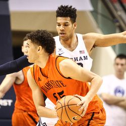 Idaho State Bengals forward Kyle Ingram (35) looks to pass around the outstretched arms of Brigham Young Cougars forward Yoeli Childs (23) as BYU takes on Idaho State at the Marriott Center in Provo on Thursday, Dec. 21, 2017.