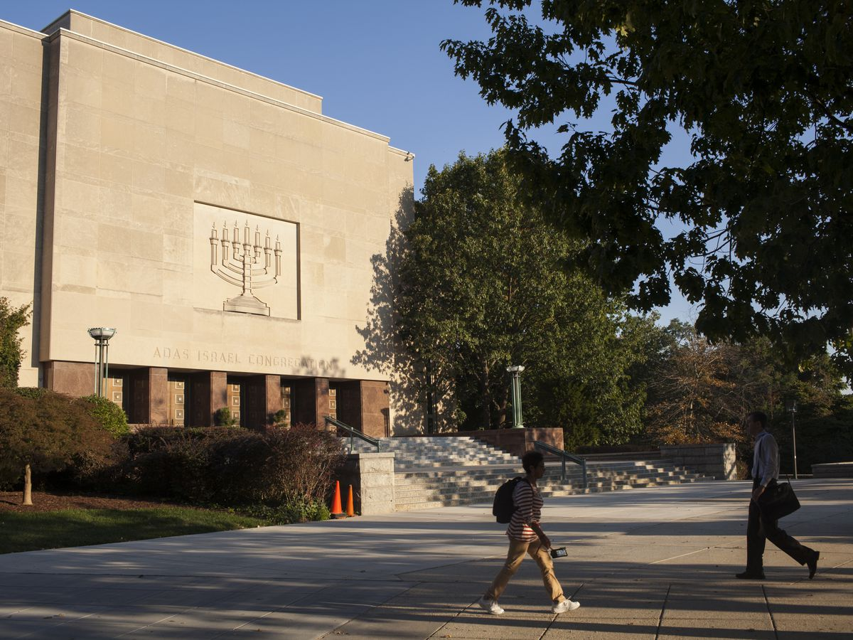 Adas Israel Congregation building. The side of the building features a menorah figure etched in stone. Tall trees are nearby.
