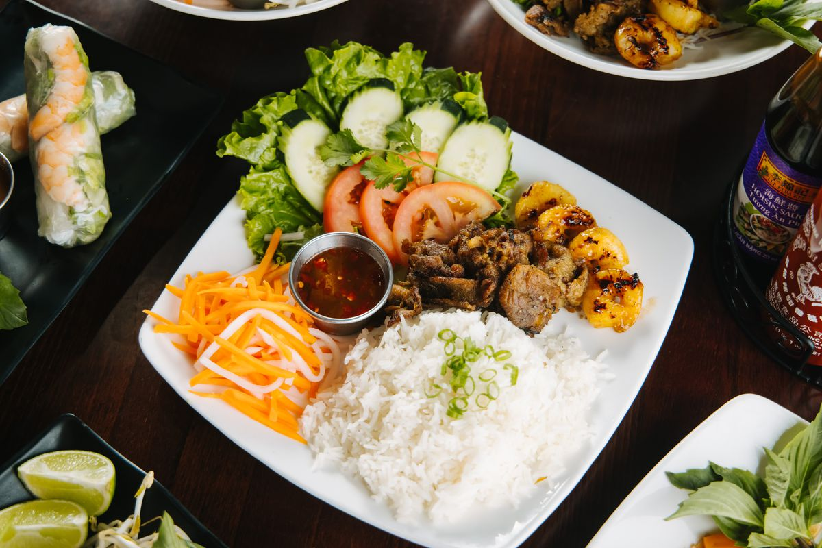A shallow square plate with a pile of rice, shredded carrots, lettuce leaves, slices cucumbers, sliced tomatoes, and more.