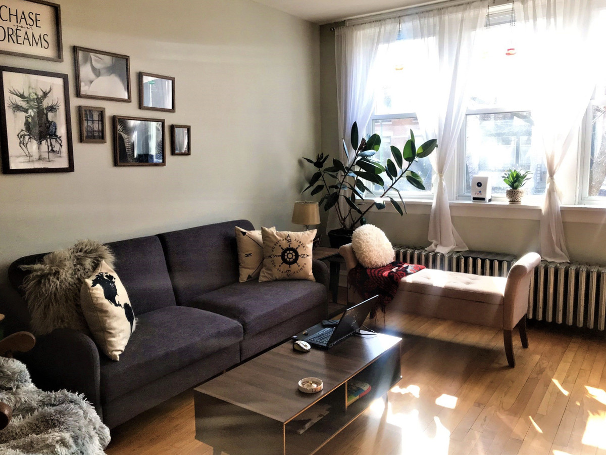A living room with a couch, an ottoman, and a wood coffee table. There is a large window and framed photos above the couch.