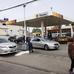 A woman walks past cars buying fuel at a petrol station in Lagos, Nigeria, Tuesday, April 24, 2012. For the price of cheap gasoline, Nigeria paid billions of dollars into a corrupt government system of fuel subsidies that saw huge contracts awarded to shady companies without any oversight, according to a lawmakers' report.