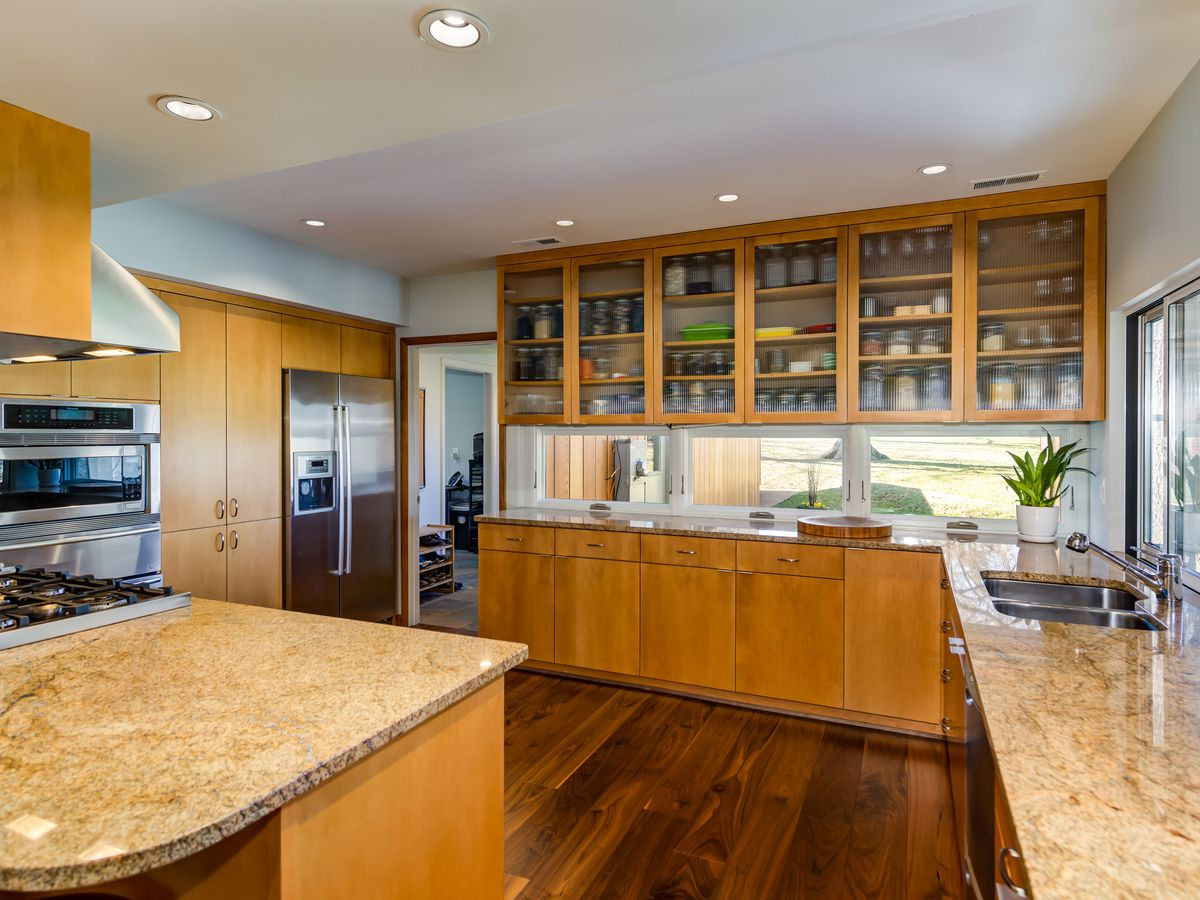 A kitchen has wooden cabinets, granite counters, and wood floors.