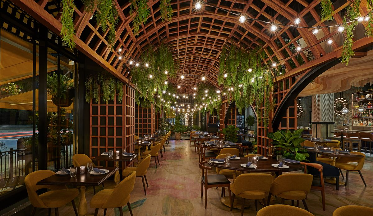 A large wooden pergola over a dining room