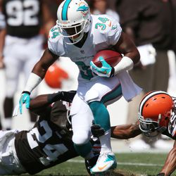 Sep 8, 2013; Cleveland, OH, USA; Miami Dolphins running back Marcus Thigpen (34) tries to avoid Cleveland Browns cornerback Johnson Bademosi (24) and cornerback Buster Skrine (22) on a punt return during the second quarter at FirstEnergy Field.